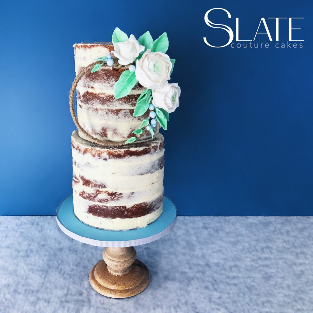 naked wedding cake with white sugar flowers