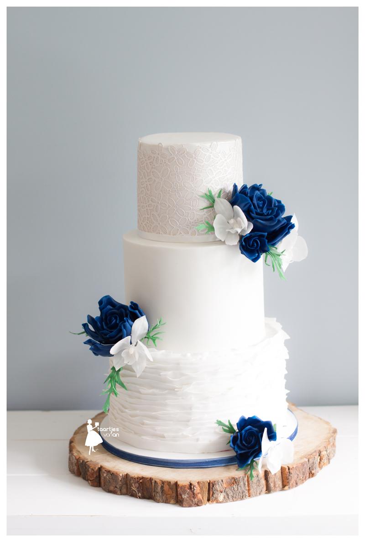 White ruffle wedding cake with navy blue sugar flowers