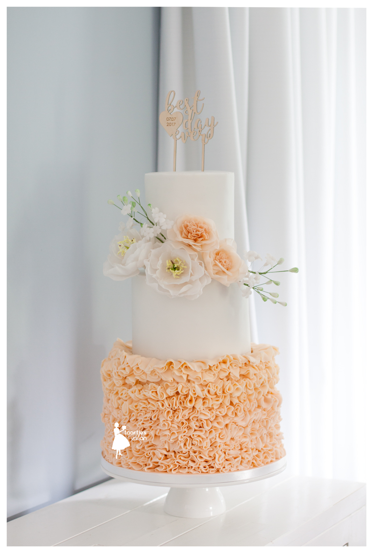 Peach and white ruffle wedding cake