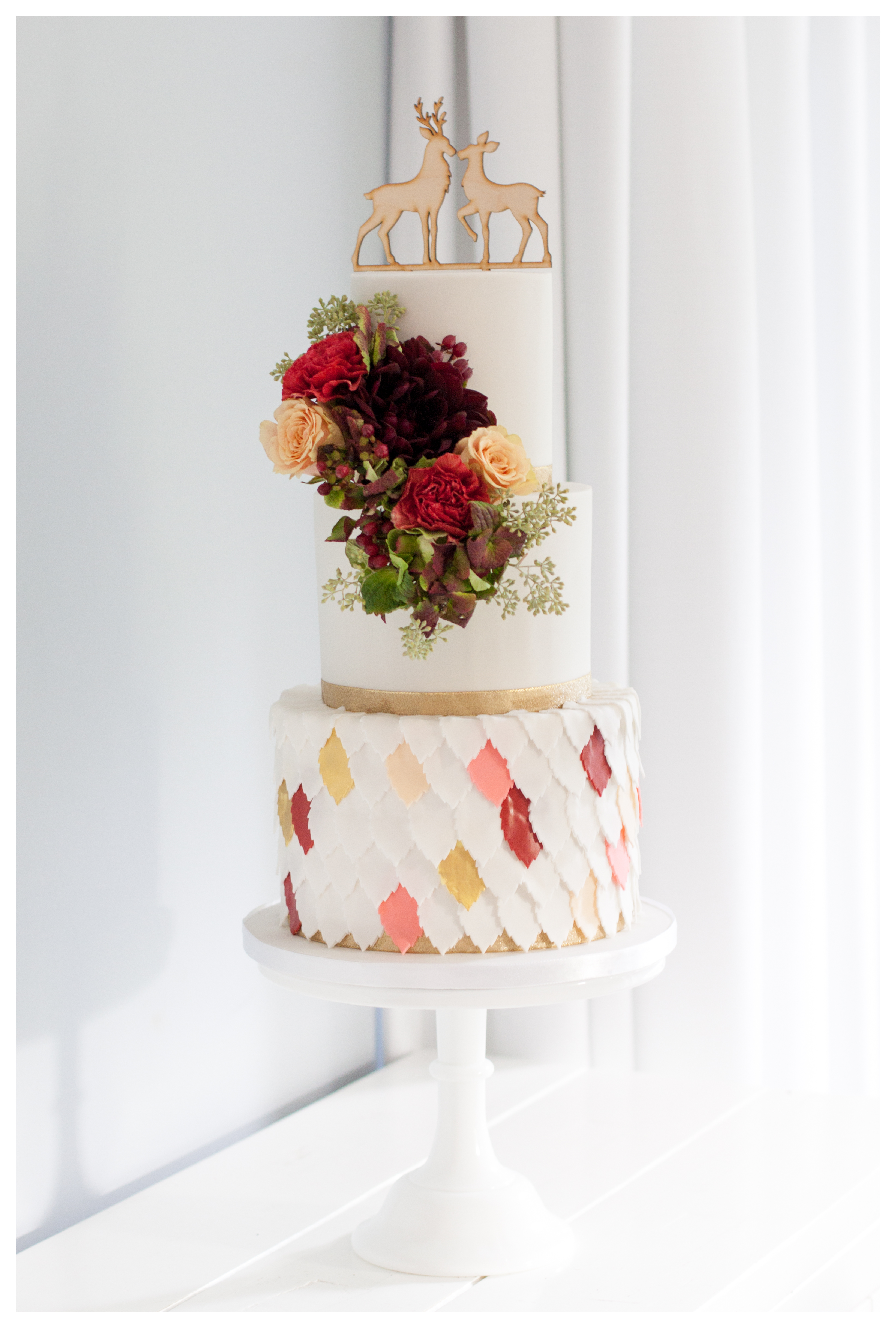 White forest themed wedding cake with scalloping