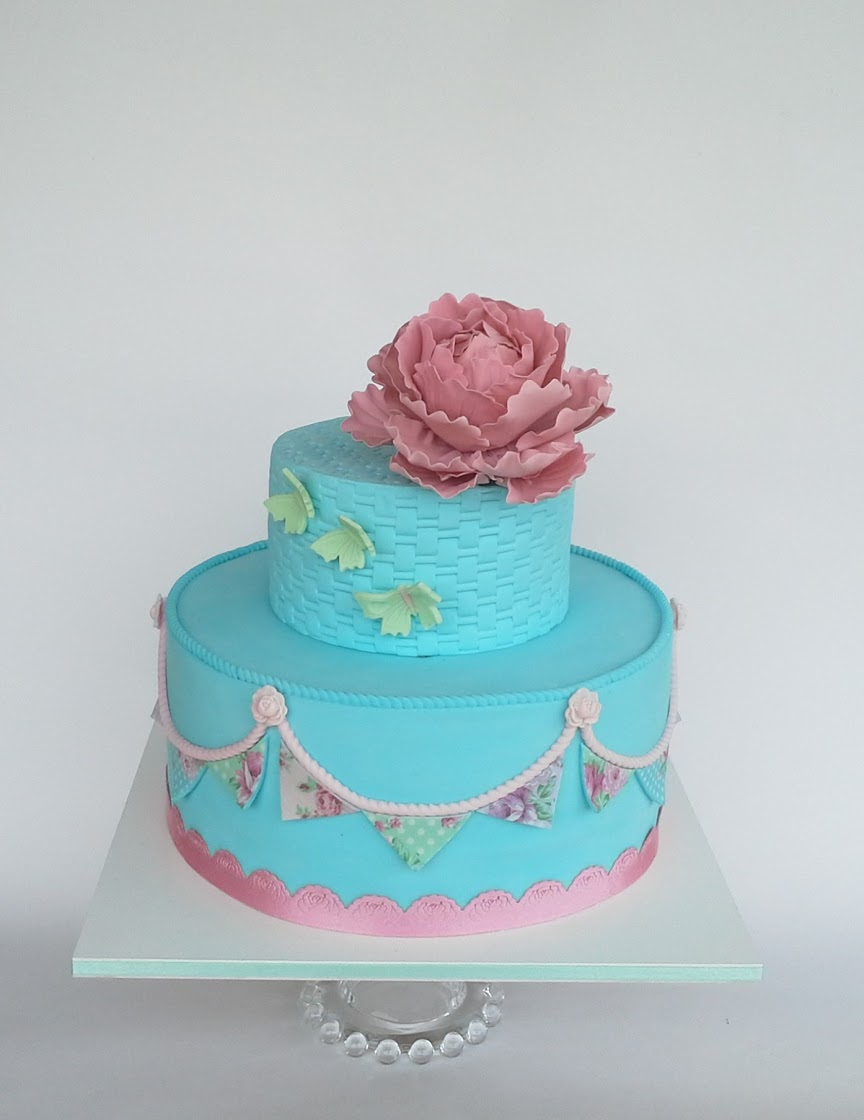 Blue birthday cake with bunting and sugar flowers