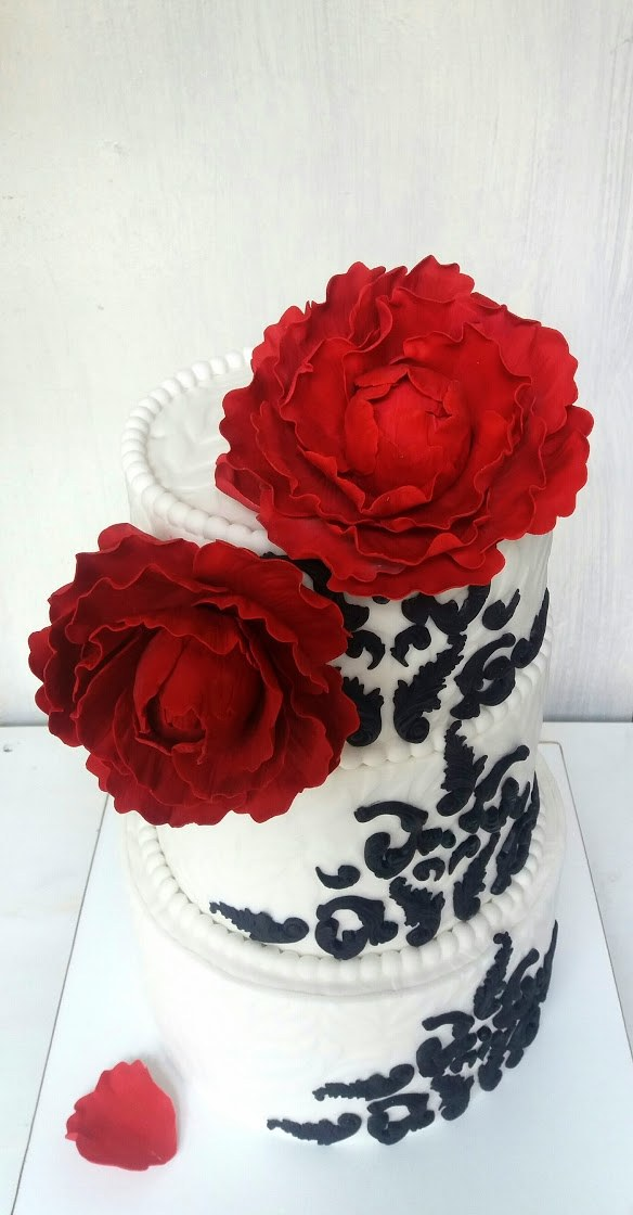 White and black wedding cake with red sugar roses