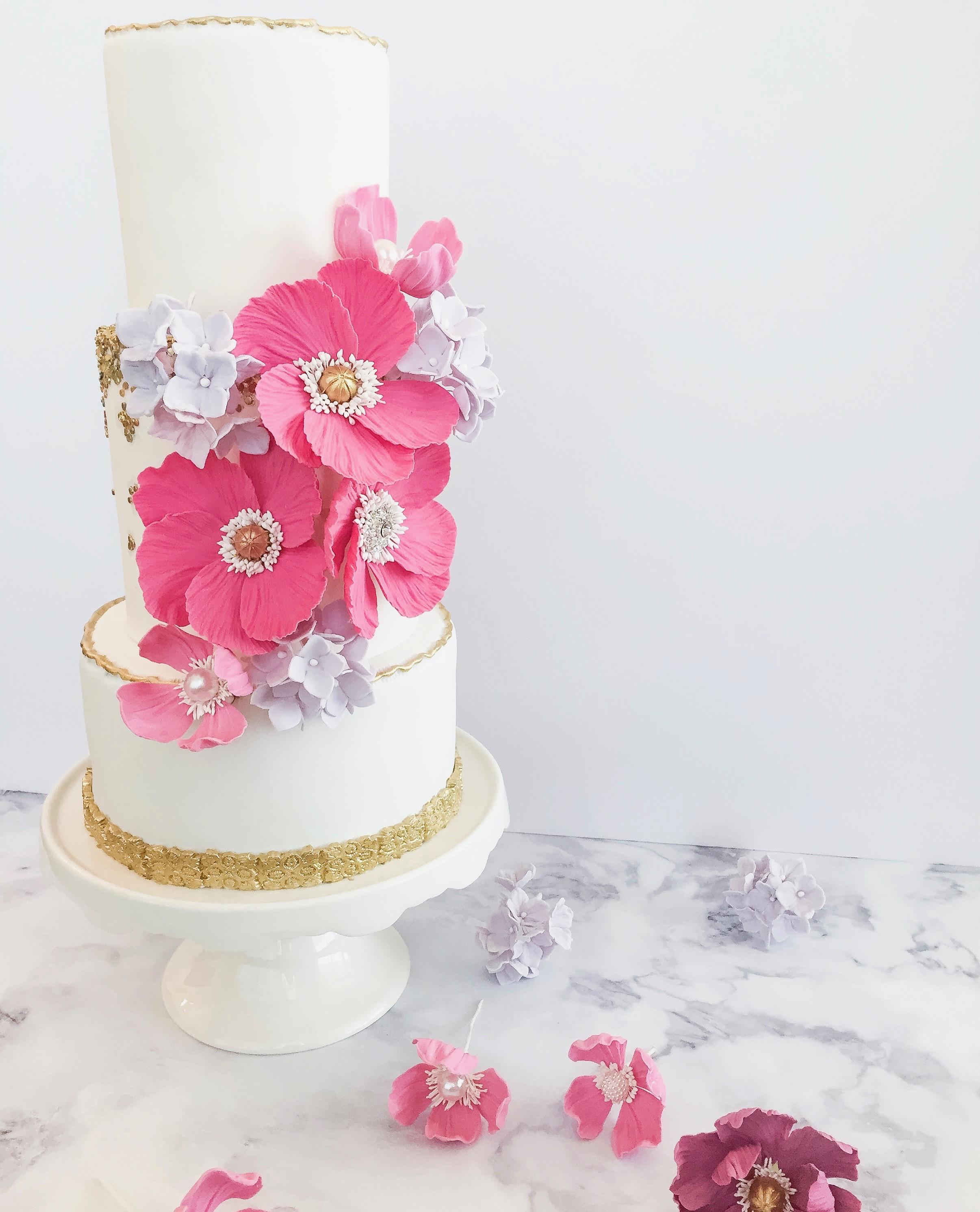White wedding cake with bright pink sugar flowers