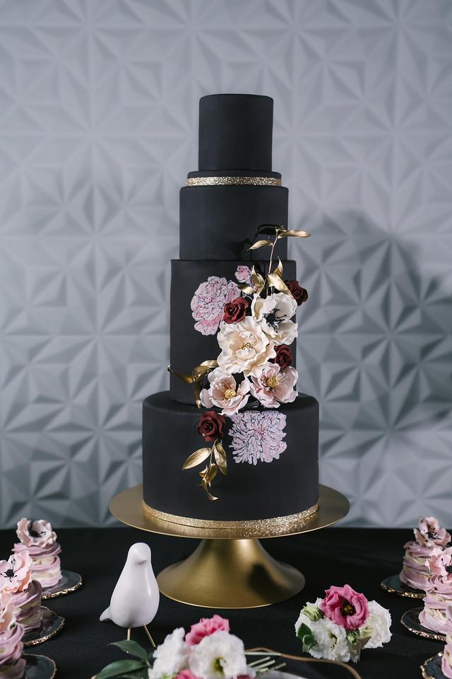 Black wedding cake with purple hued sugar flowers