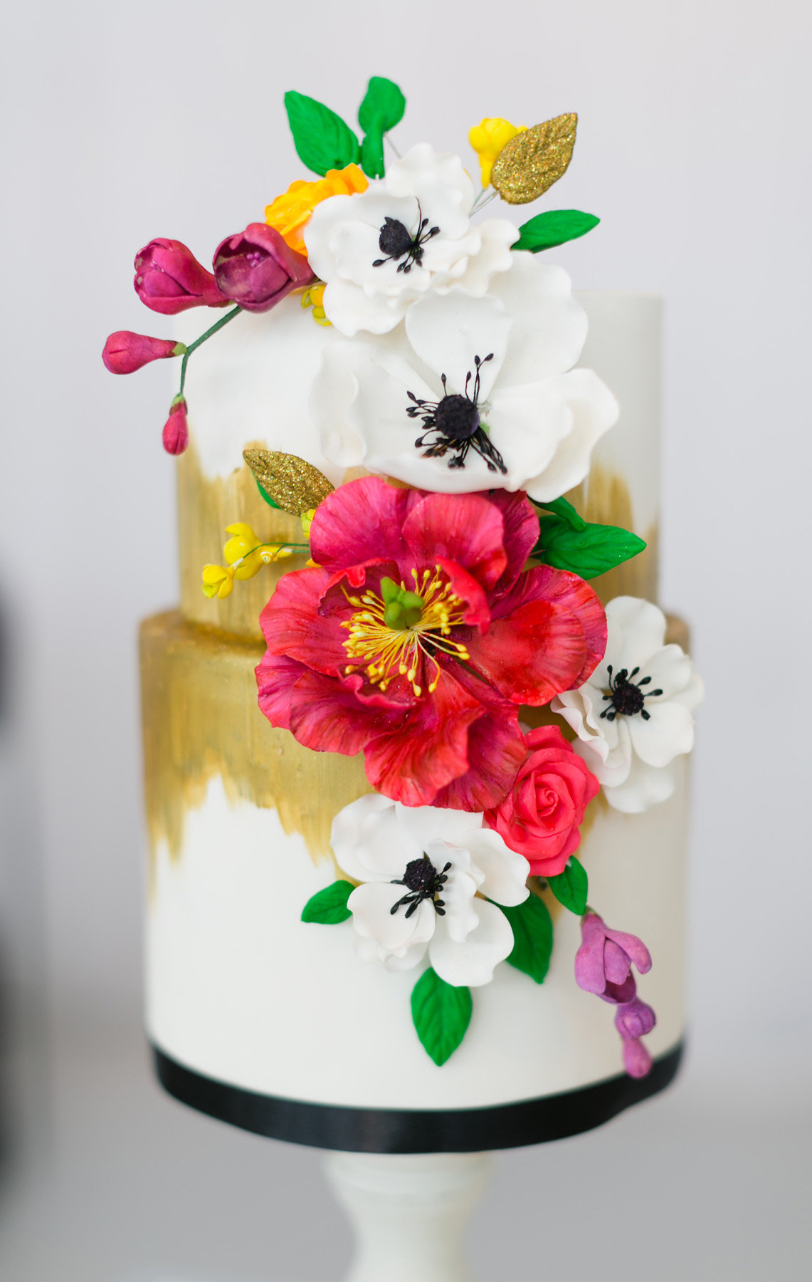 White wedding cake with gold paint and sugar flowers