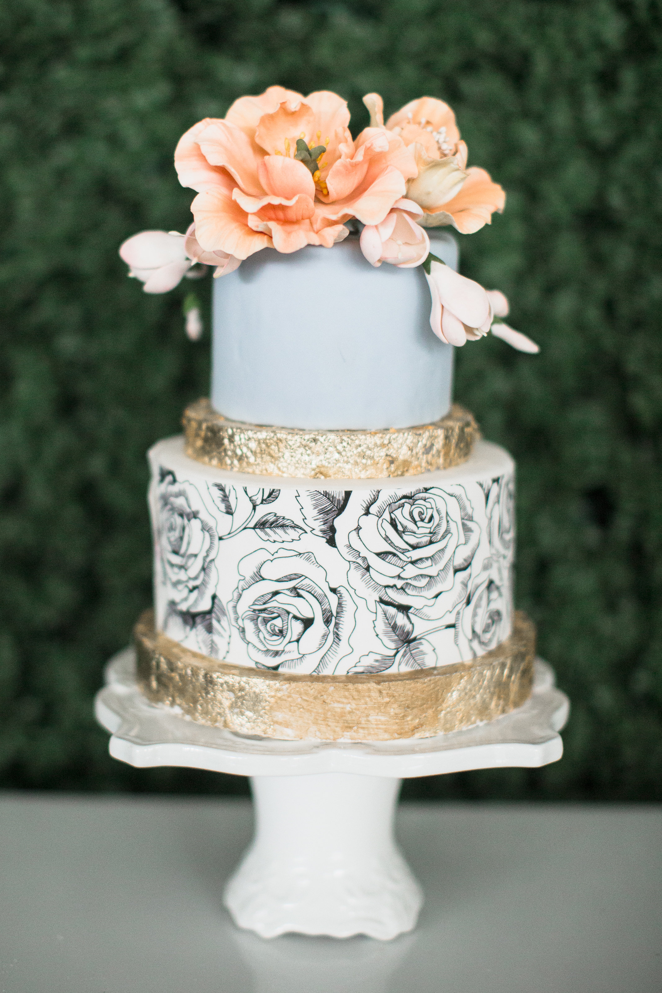 Light blue wedding cake with hand painted black roses and gold accents