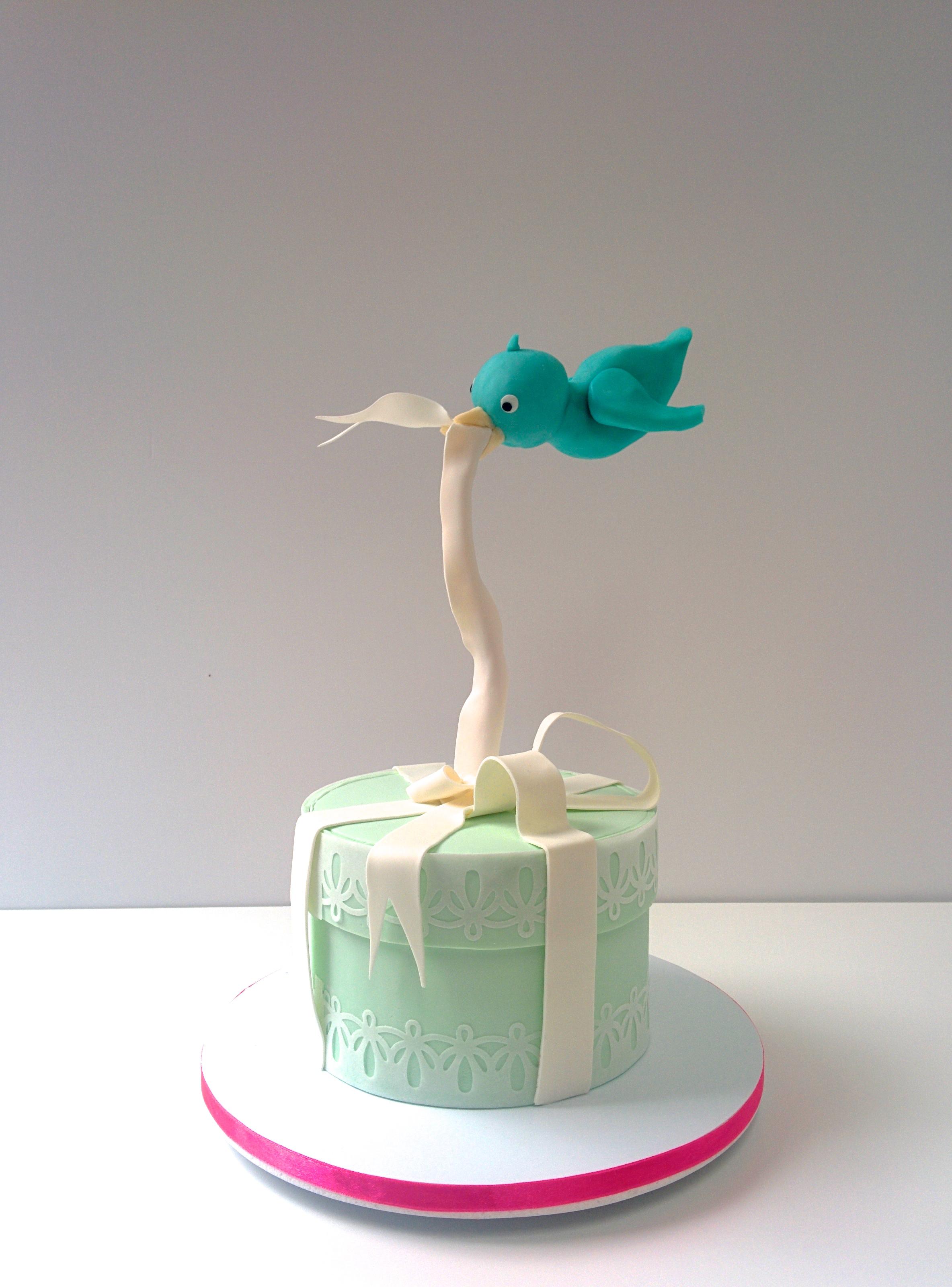 Gravity defying blue bird and ribbon cake