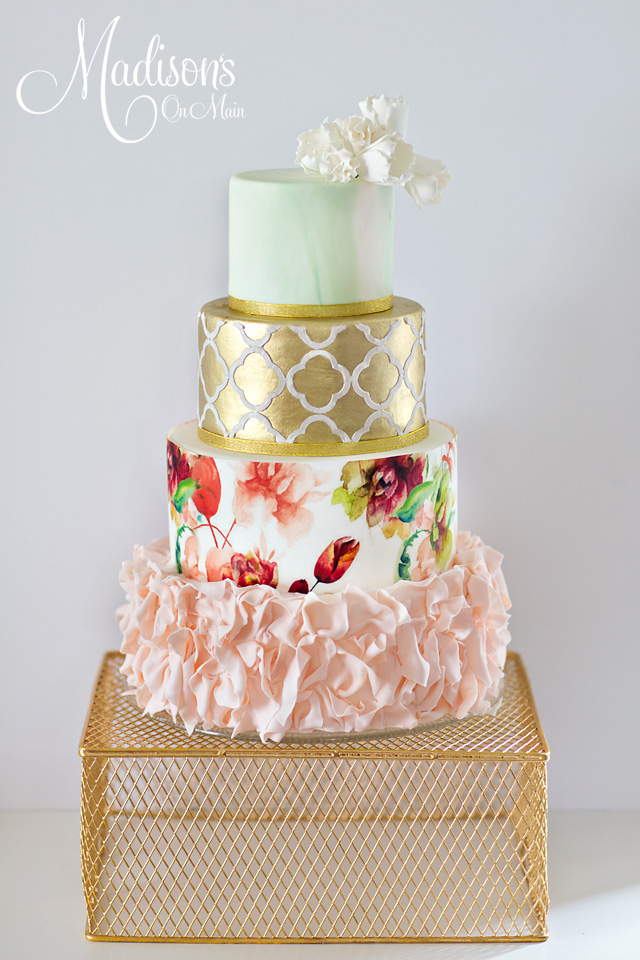 Gold damask pattern wedding cake with pink ruffles and sugar flowers