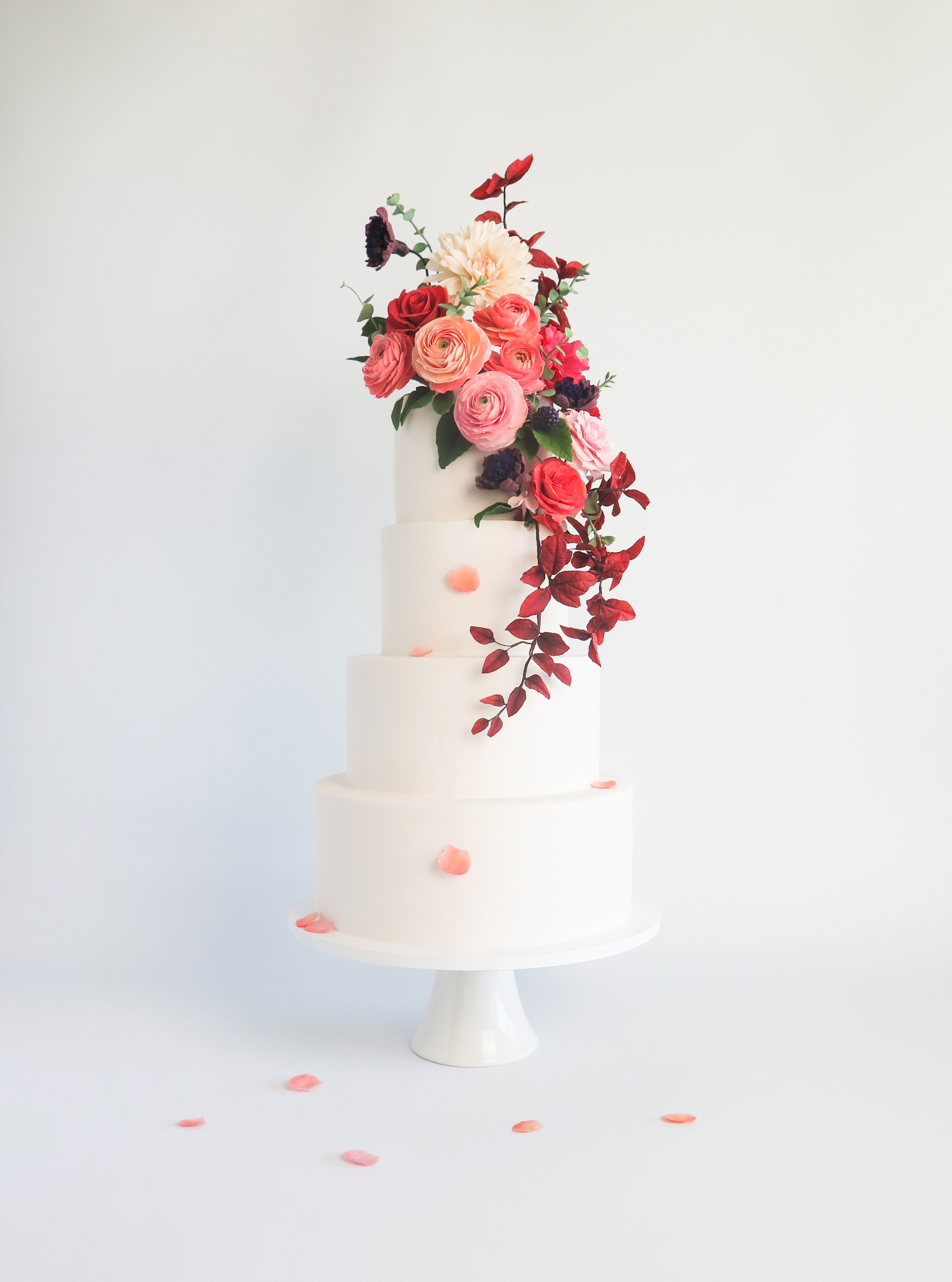 White wedding cake with cascading rich colored sugar flowers