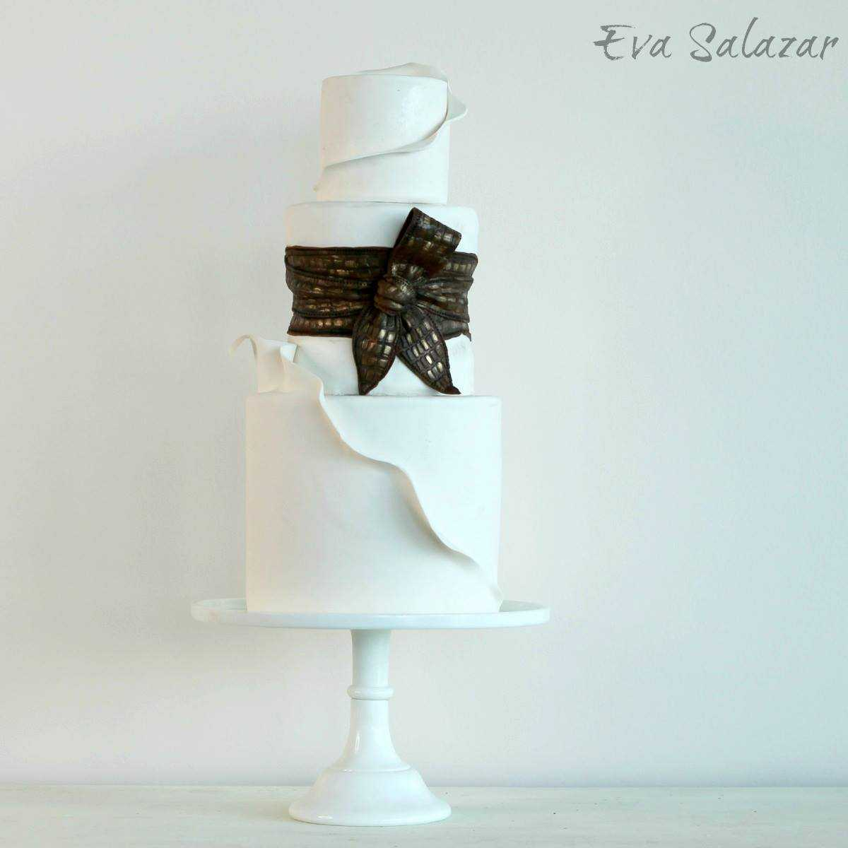 White wedding cake with copper bow
