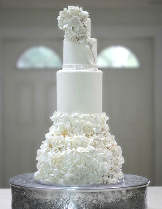 All white luxe wedding cake with ruffles