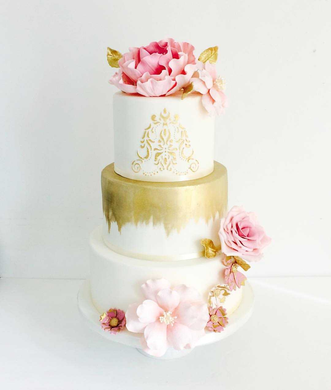 Ivory wedding cake with gold drip and pink sugar roses