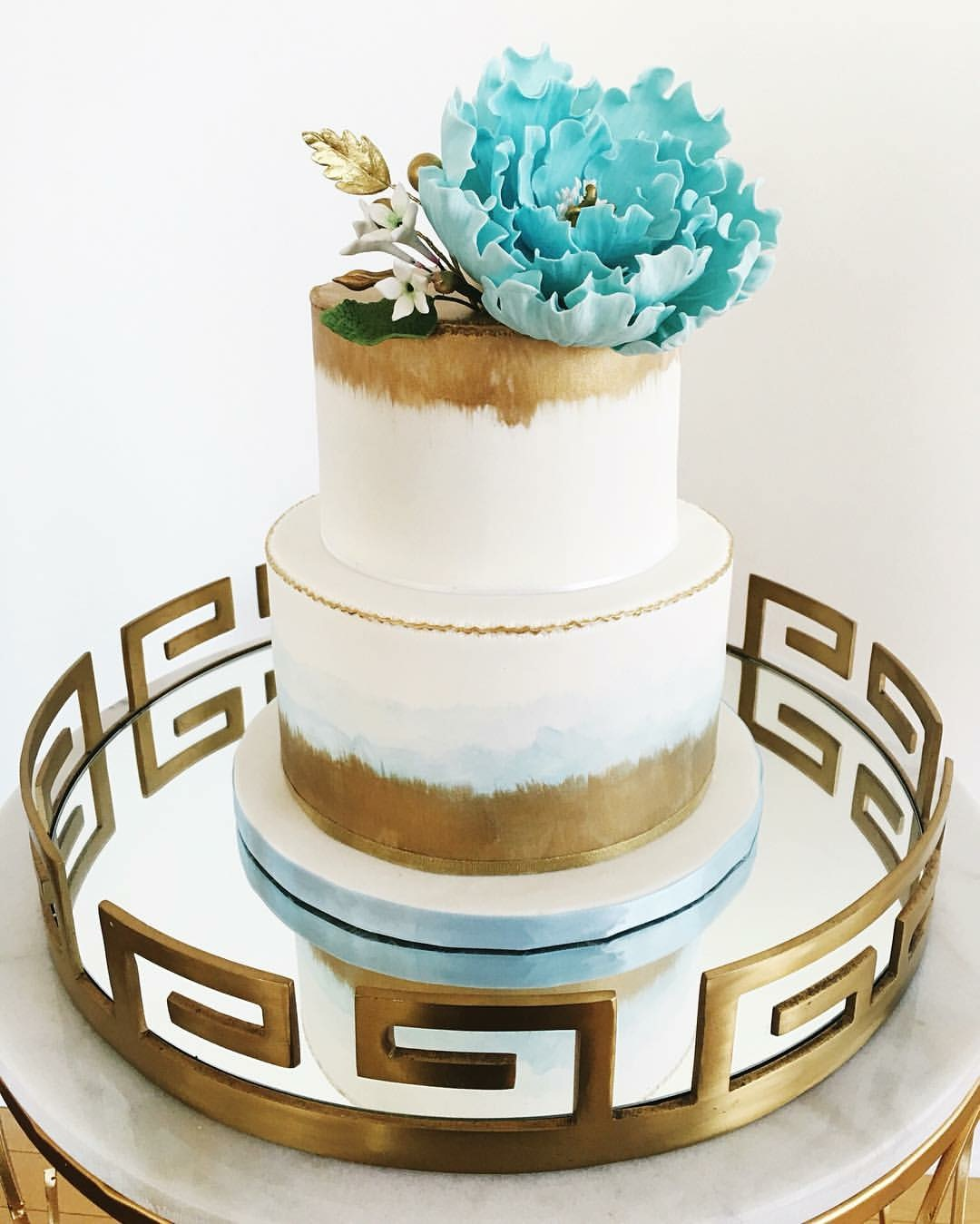 White and gold wedding cake with blue sugar flower