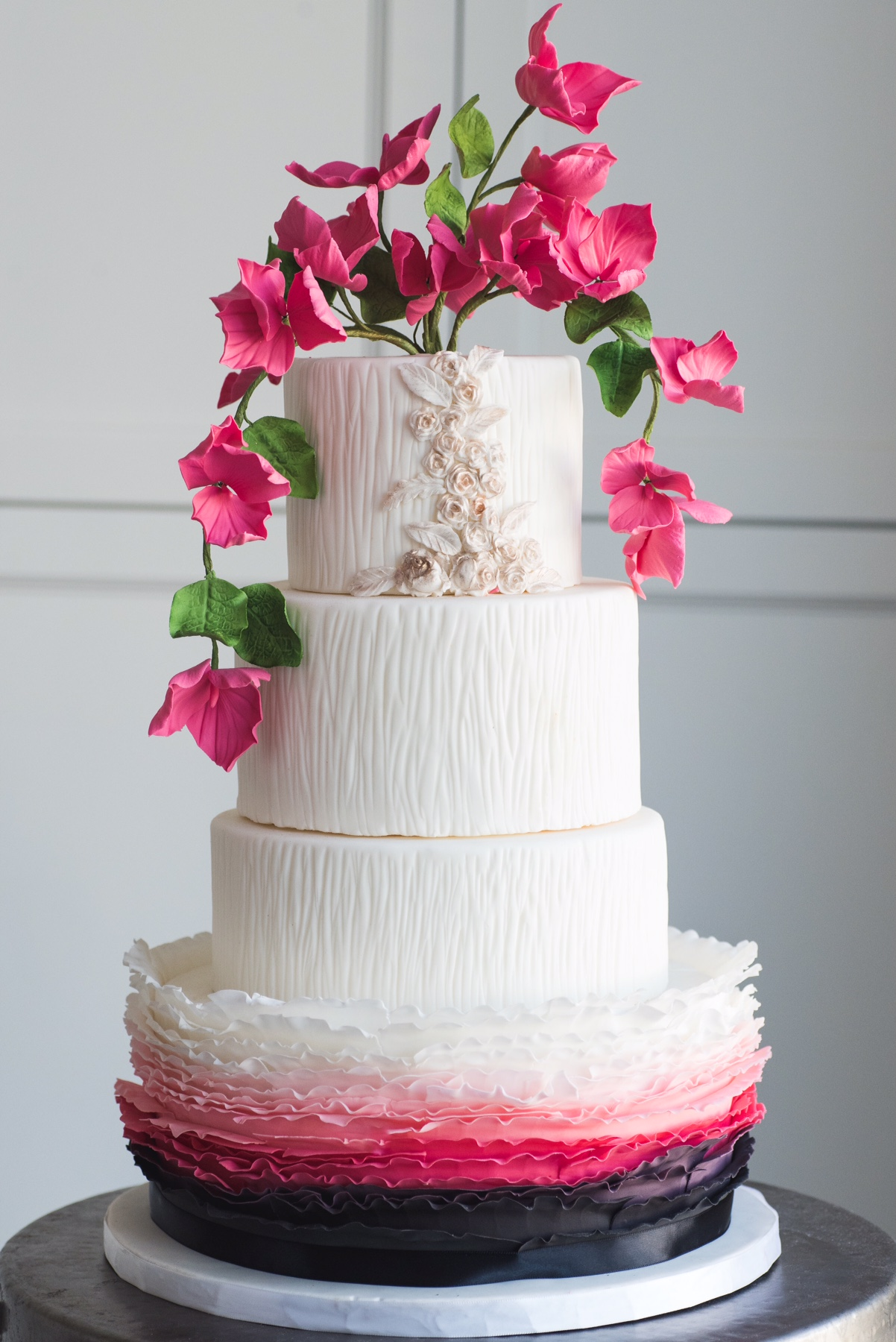 White wedding cake with pink and black ombre ruffles