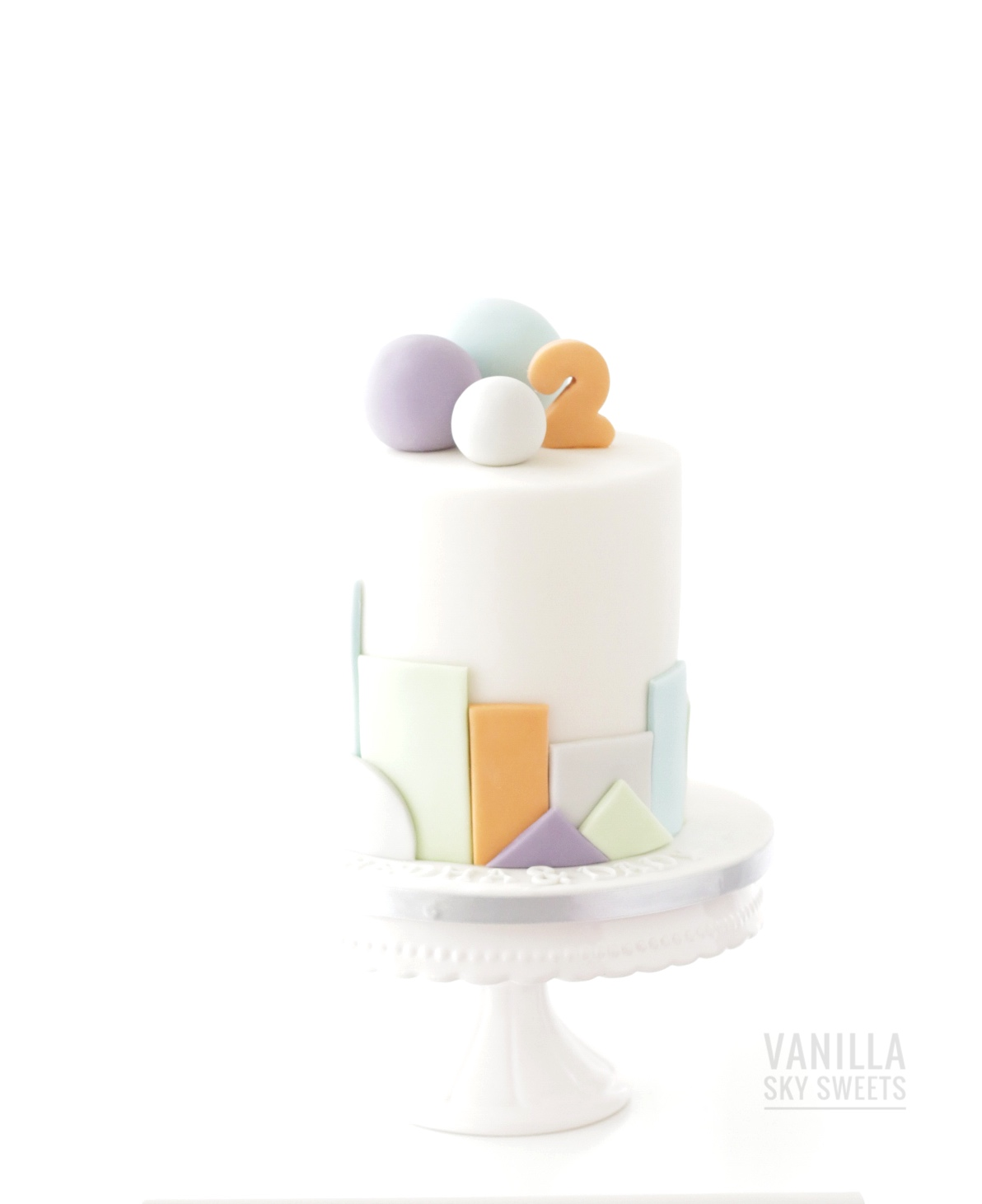 Mini white birthday cake with pastel color bubbles