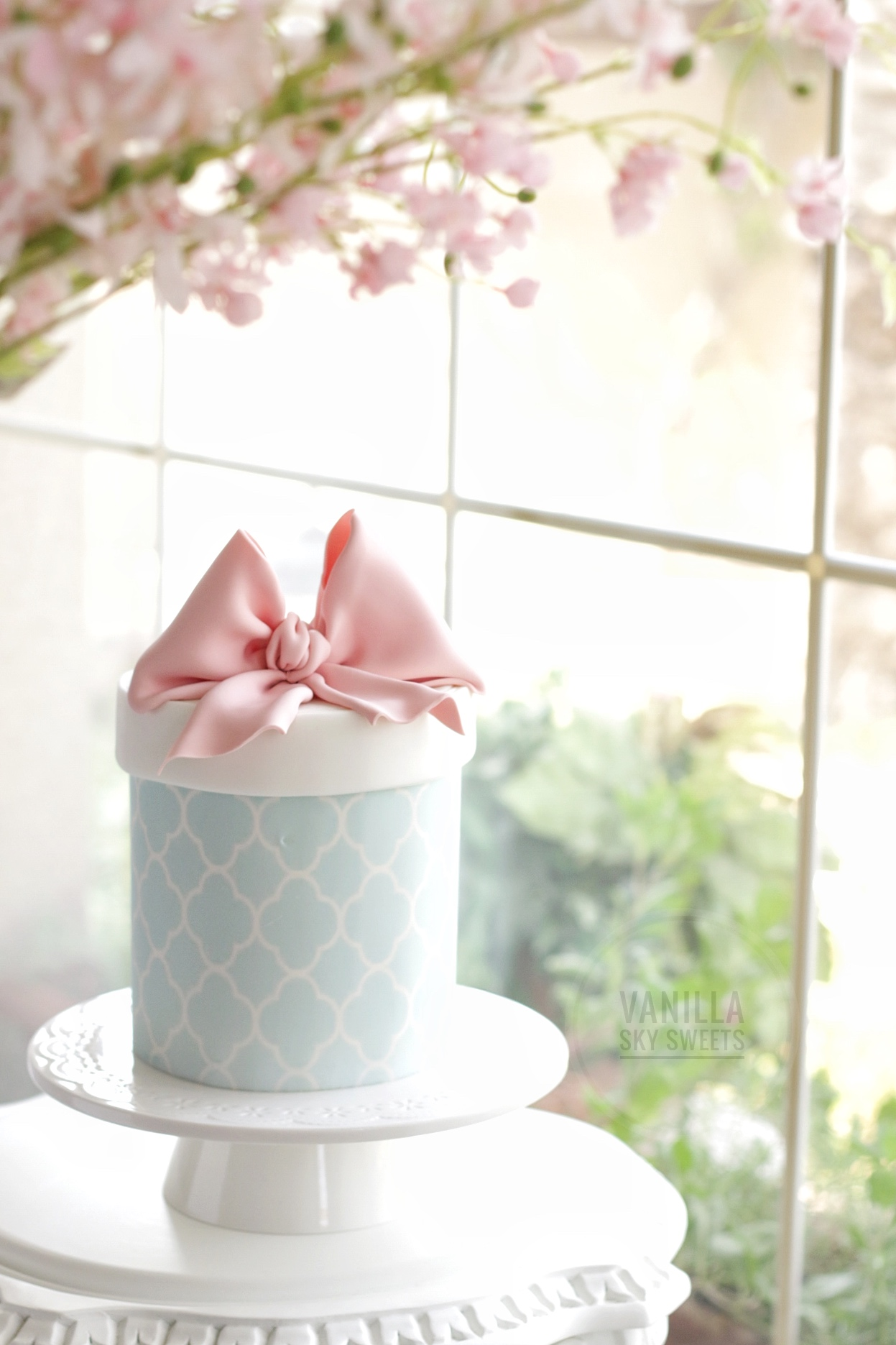 Light blue and white fondant gift box cake with pink bow on top