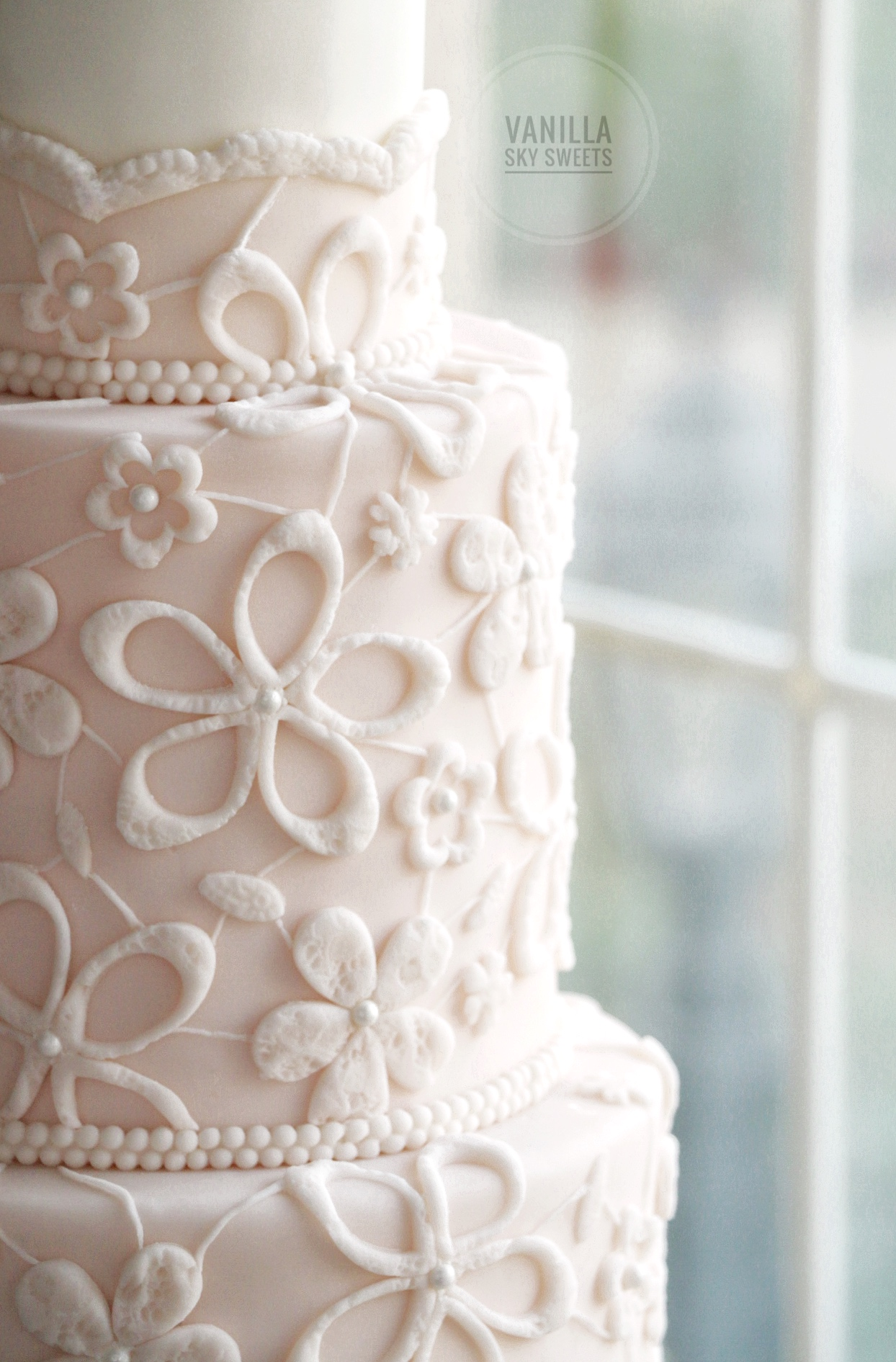Light pink and white embroidered wedding cake