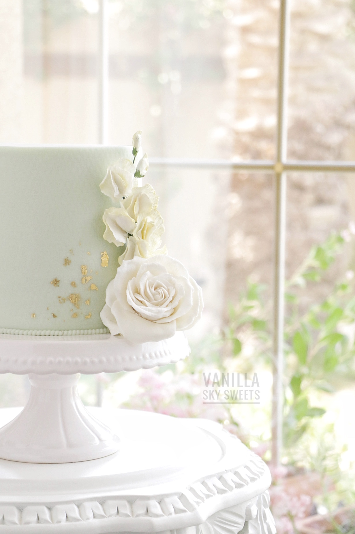 Pastel green mini wedding cake with gold and sugar flowers