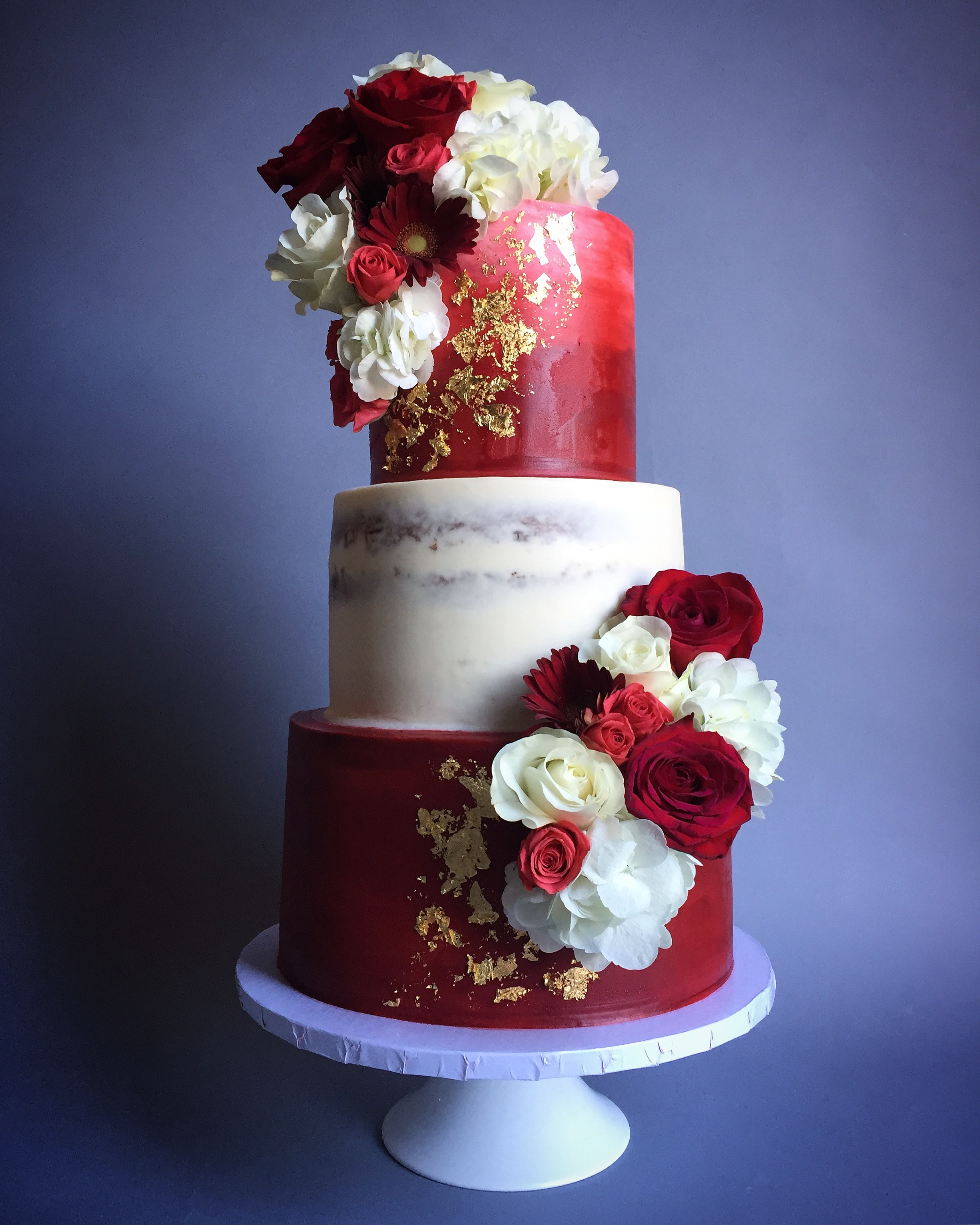 Red and white semi naked wedding cake with sugar flowers