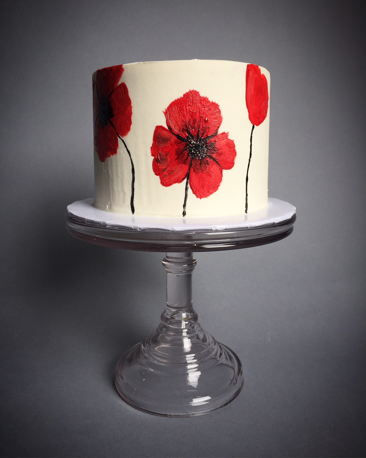 White wedding cake with hand painted red poppies