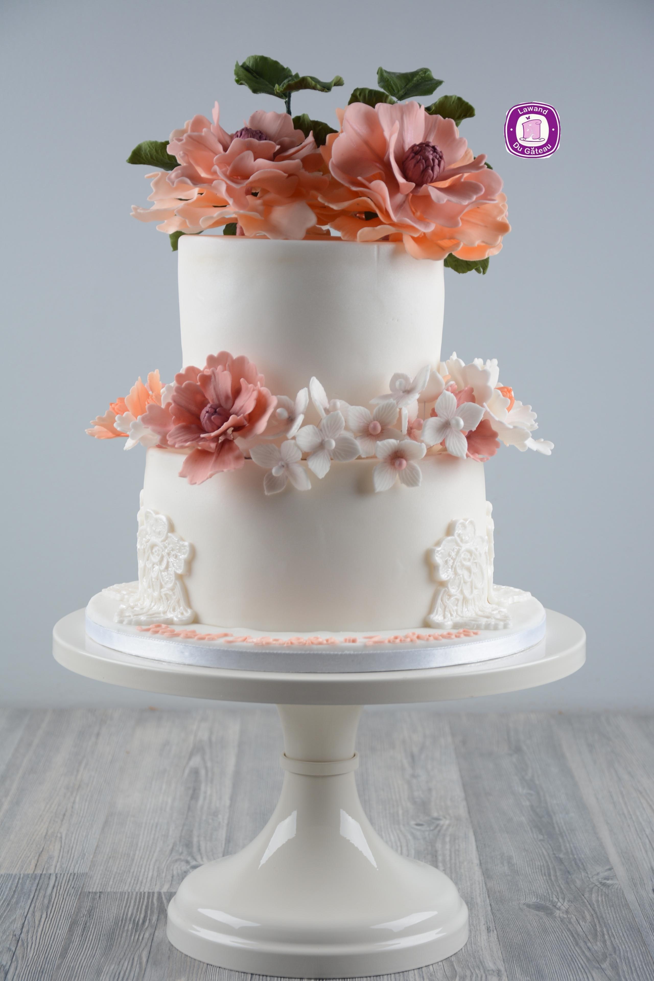 White wedding cake with orange and pink sugar flowers