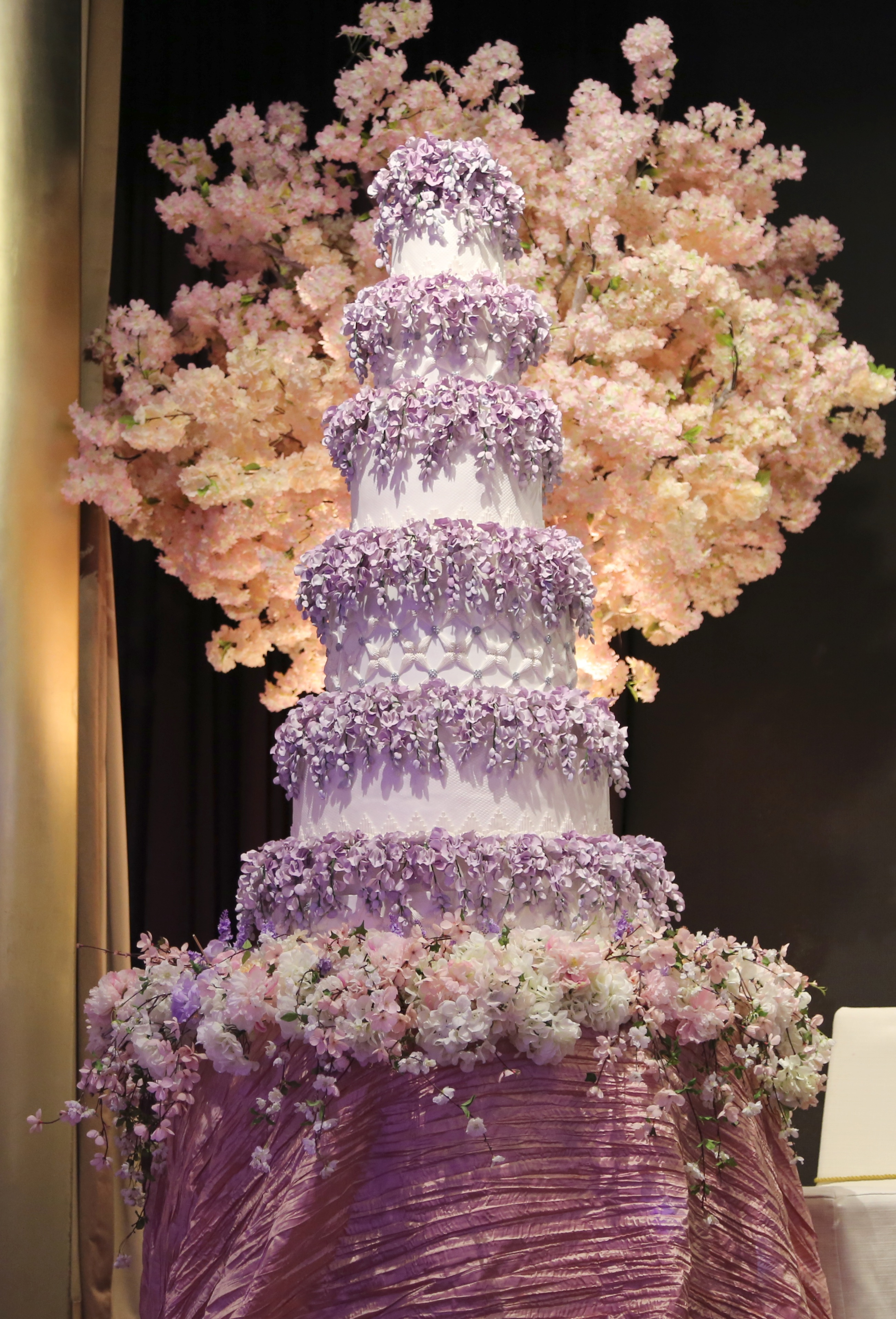 Tall tiered white wedding with purple sugar flowers