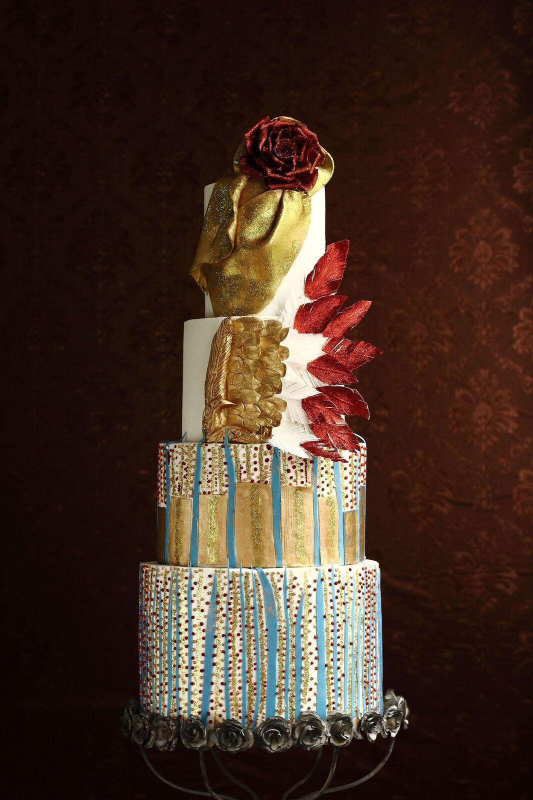 Gold and white Avant Garde wedding cake with red feathers