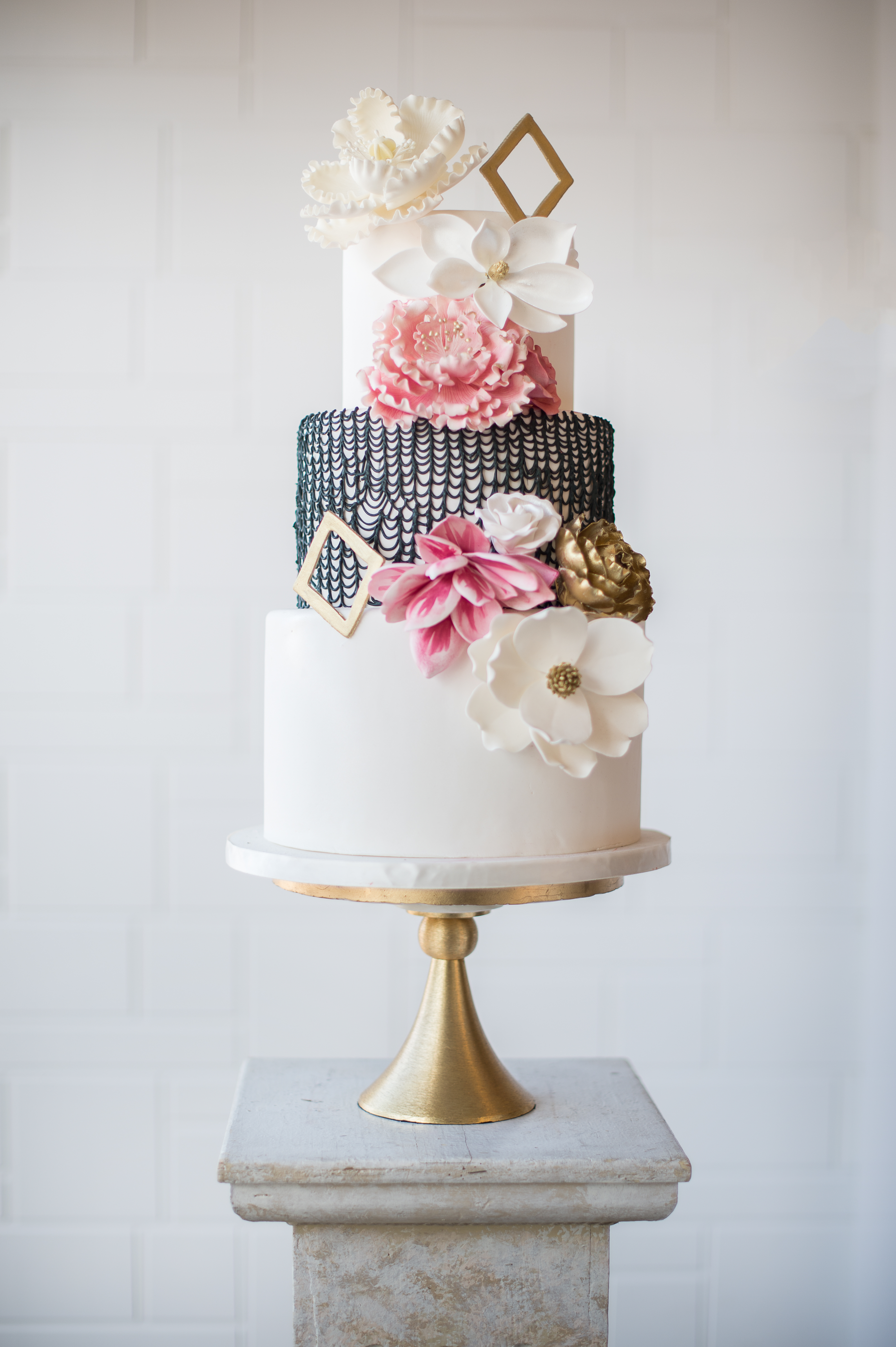 Ivory with black wedding cake with geometric shape and sugar flowers