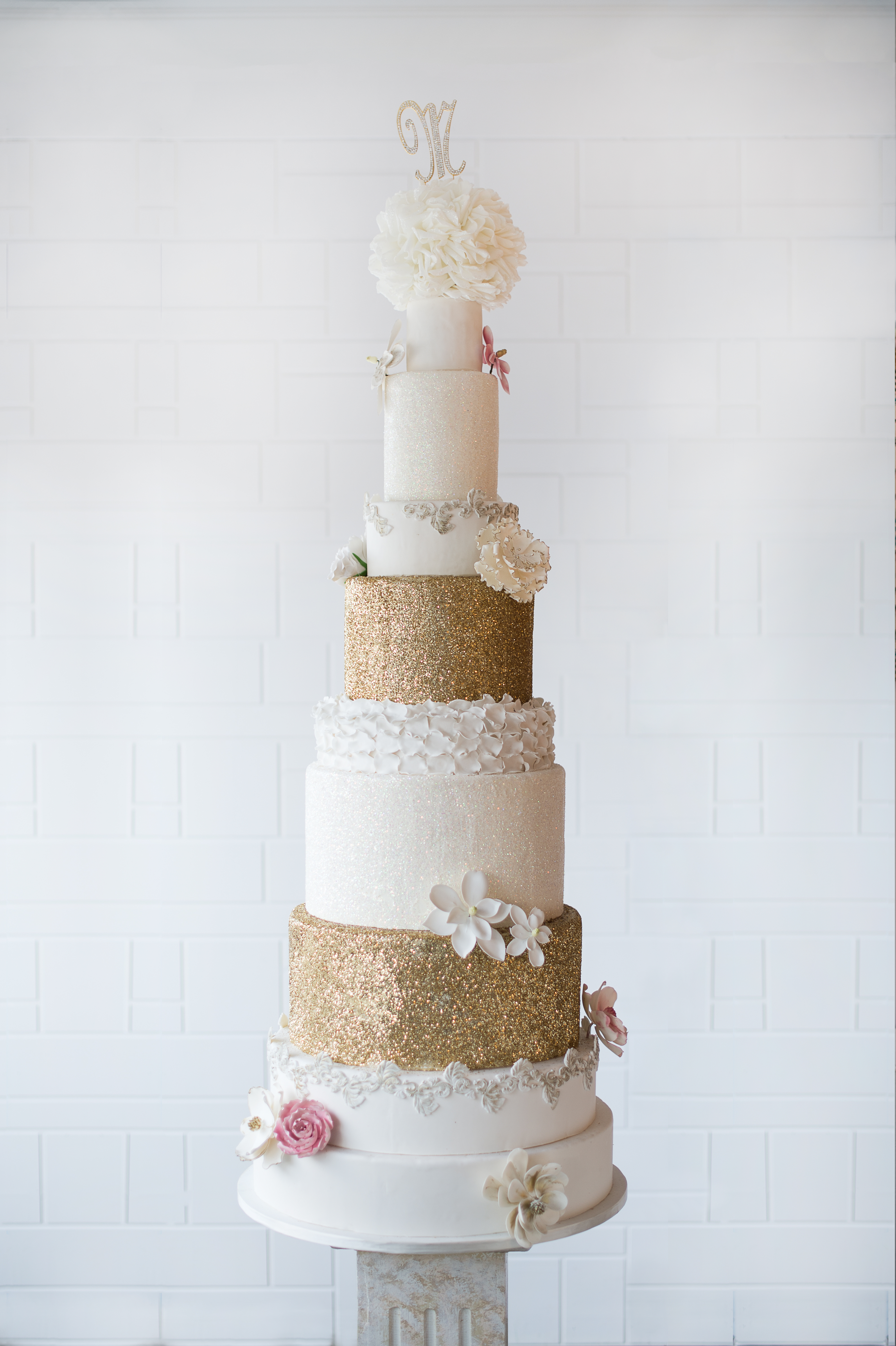Tall tiered wedding cake with ivory and copper sparkle
