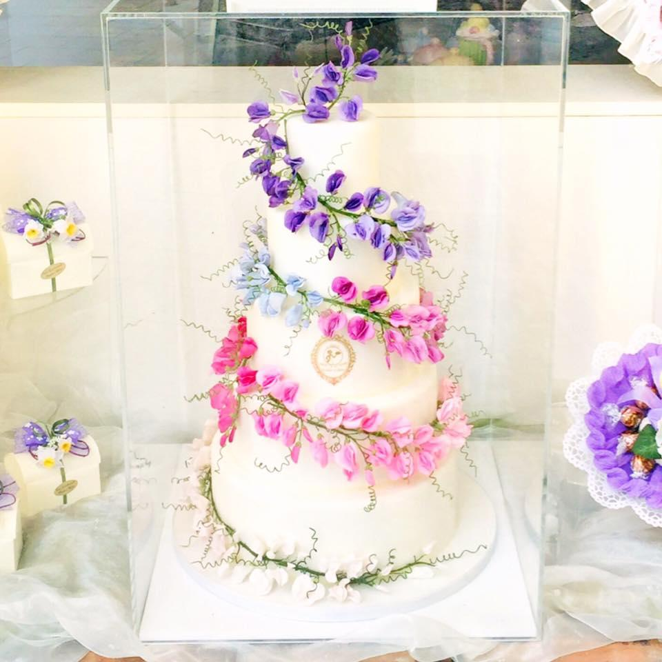 White wedding cake with pastel sugar leaves