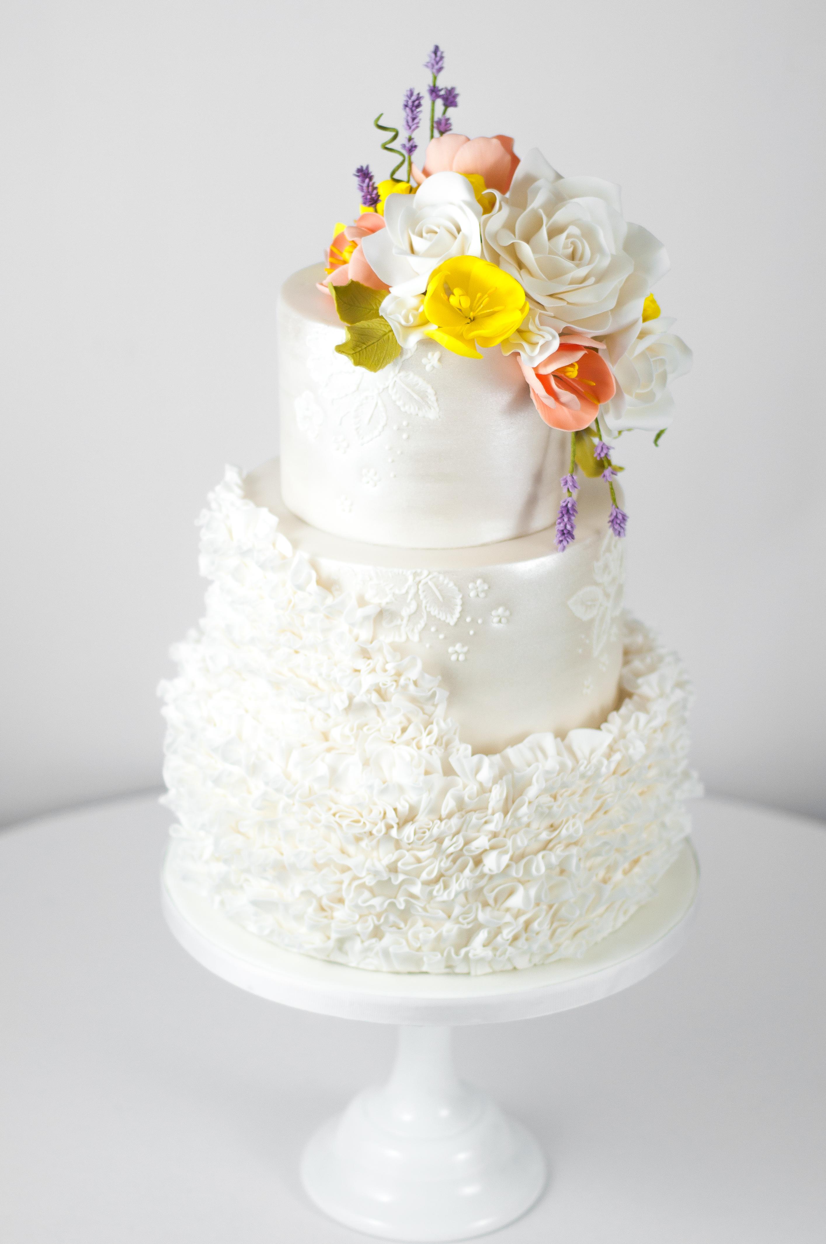 White ruffle wedding cake with tulip sugar flowers