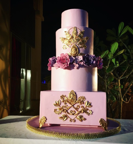 Purple wedding cake with gold sugar decor and sugar flowers