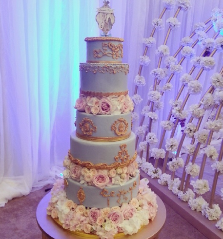 Light blue ornate wedding cake with gold embossing and sugar roses