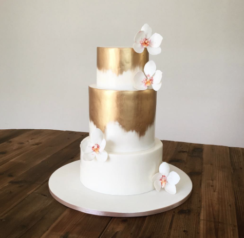 Gold and white wedding cake with sugar flowers