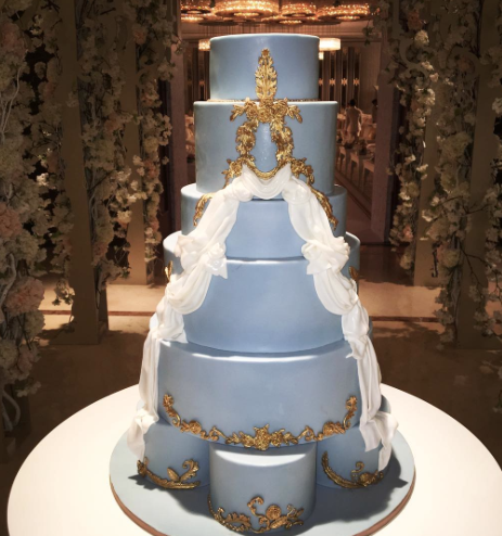 Tall blue wedding cake with gold