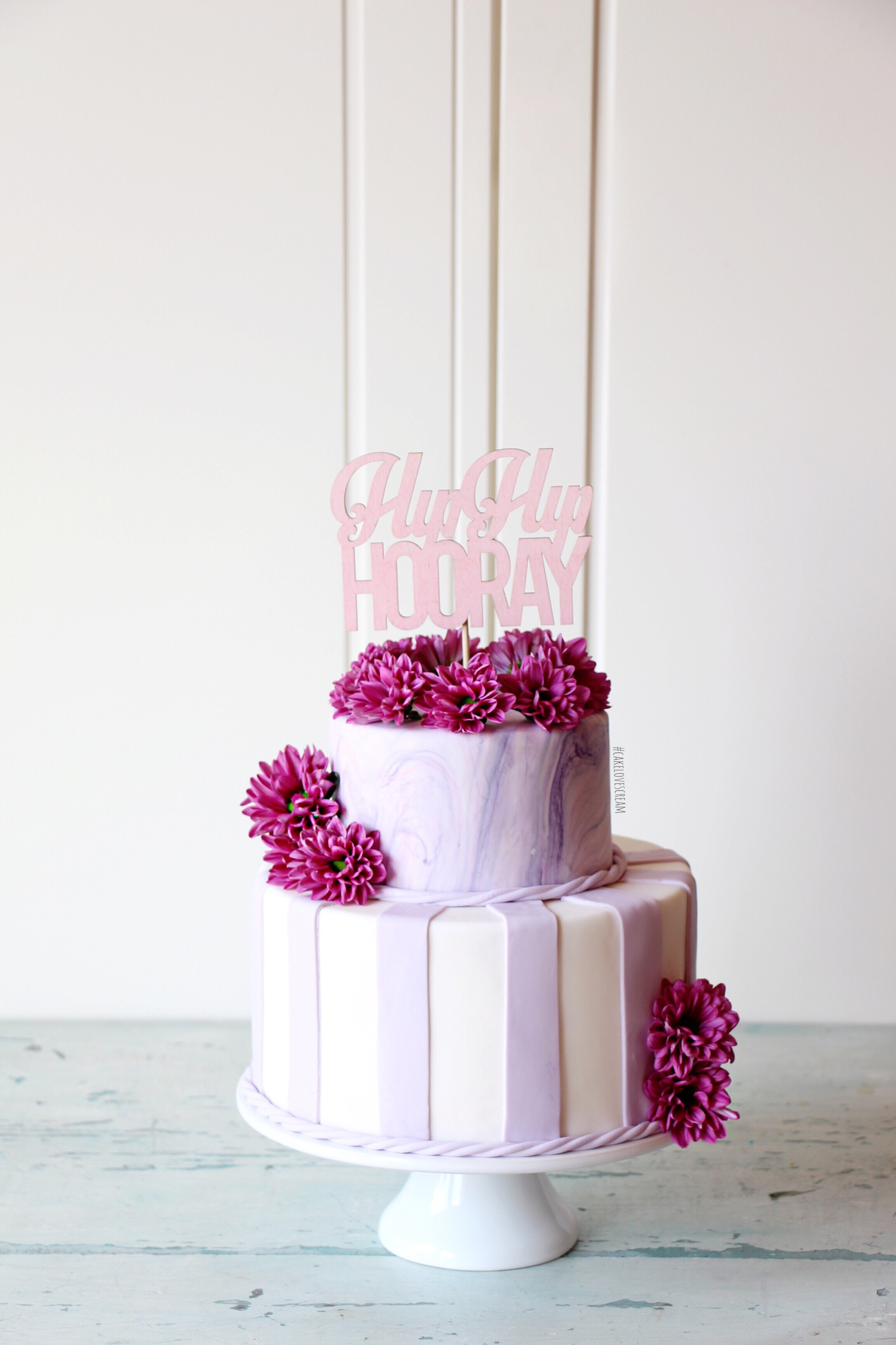 Purple and white striped cake with sugar flowers