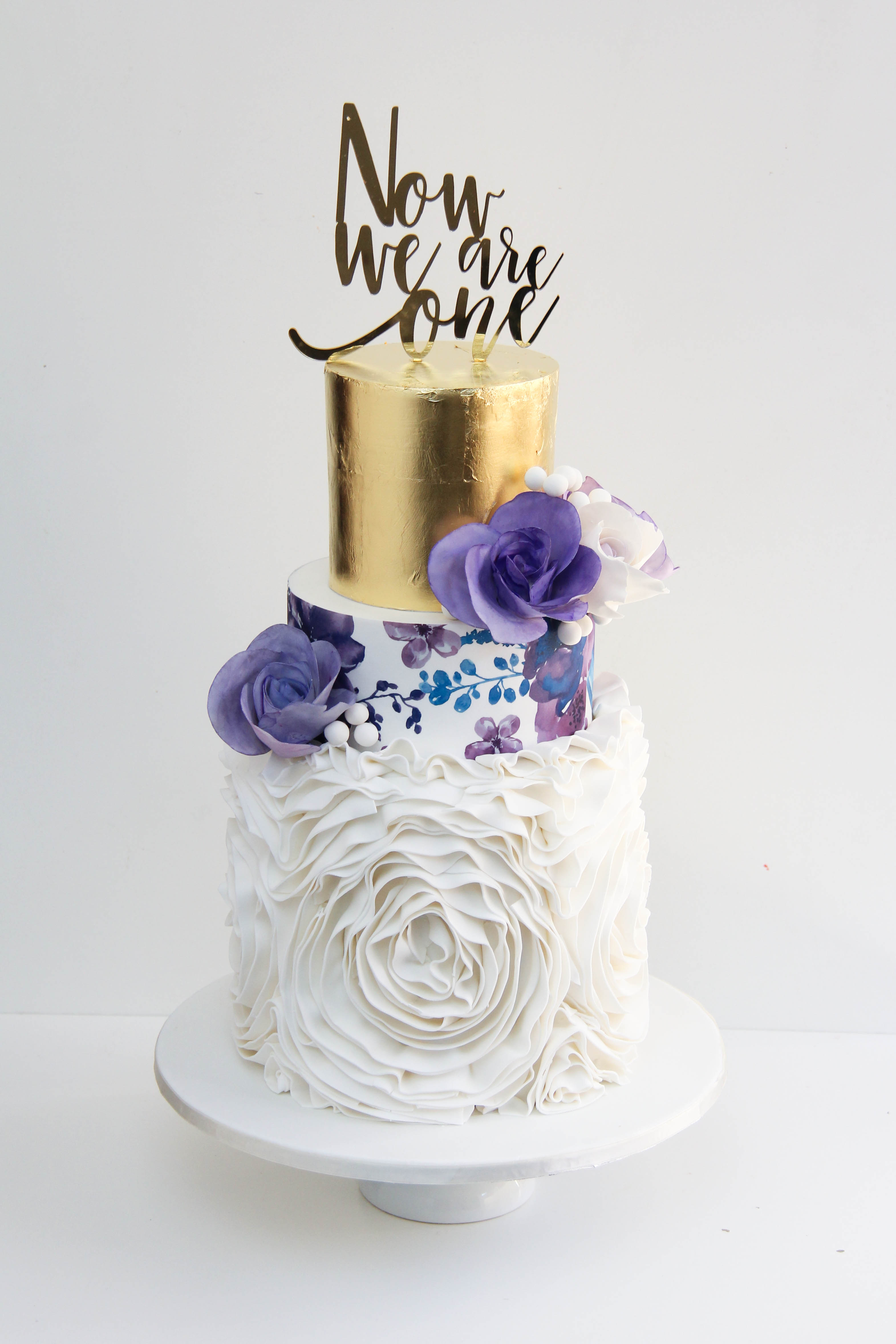 Gold and white wedding cake with rosettes