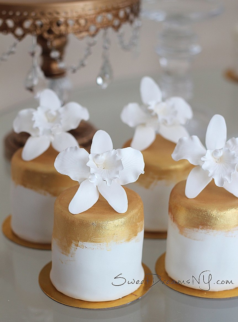 White petit fours with sugar flowers and gold leaf