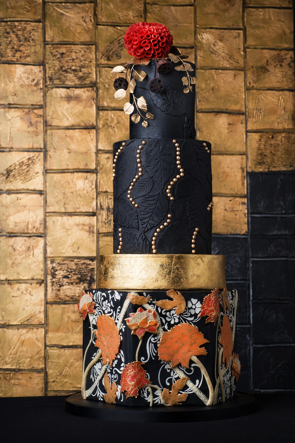 Black wedding cake with gold and orange appliqué
