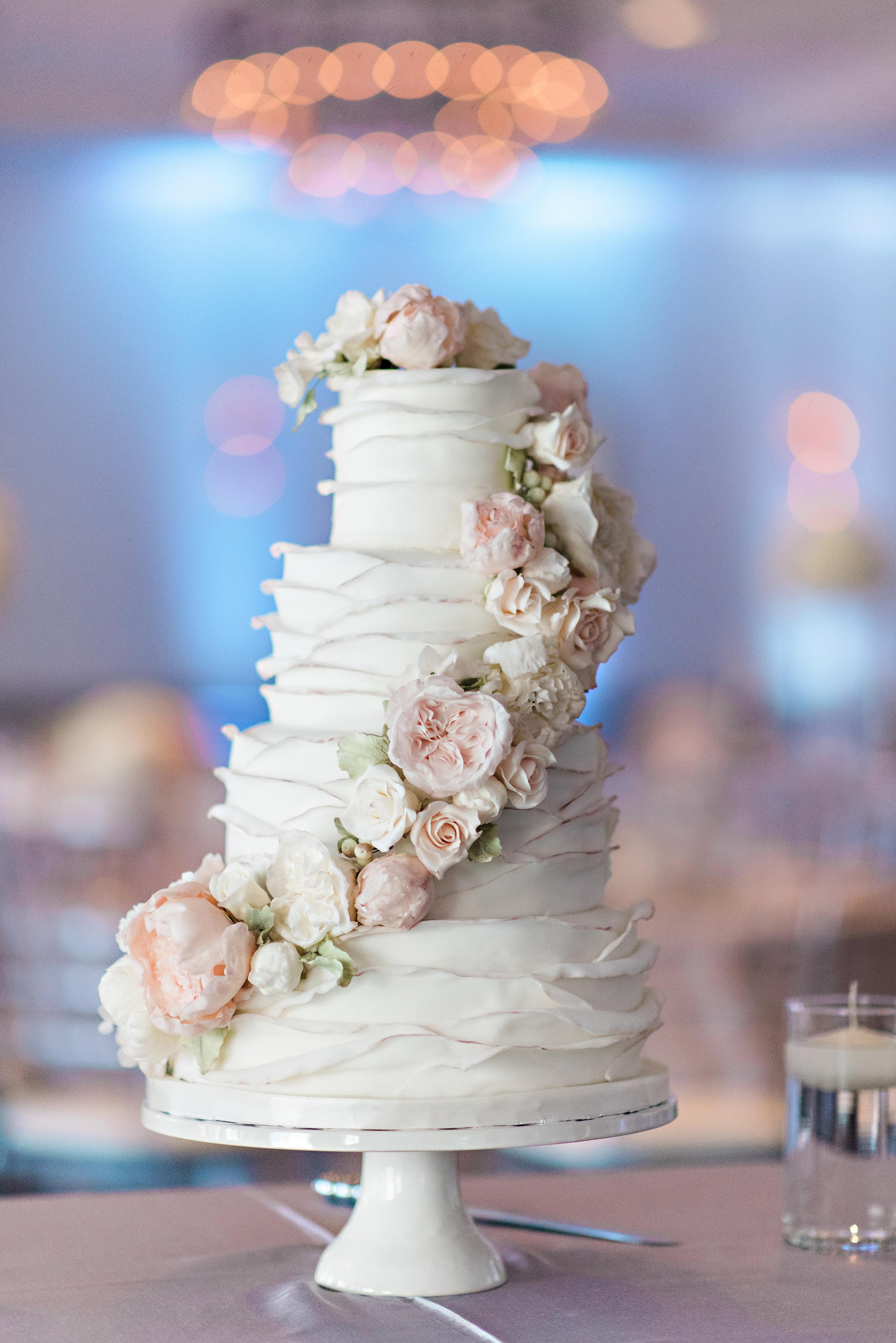 White fondant ruffled wedding cake with cascading sugar flowers