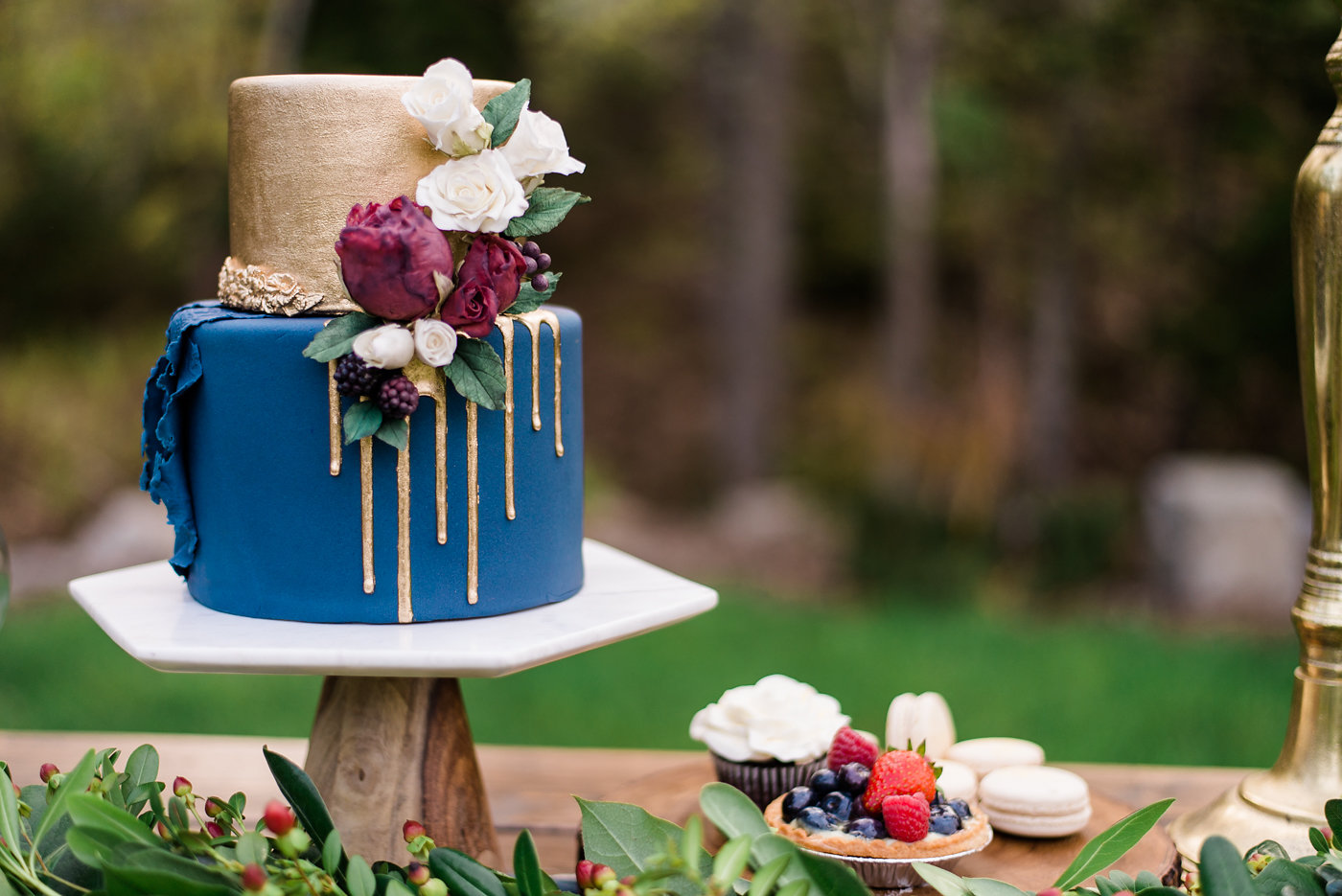 Blue and gold drip wedding cake with burgundy sugar flowers