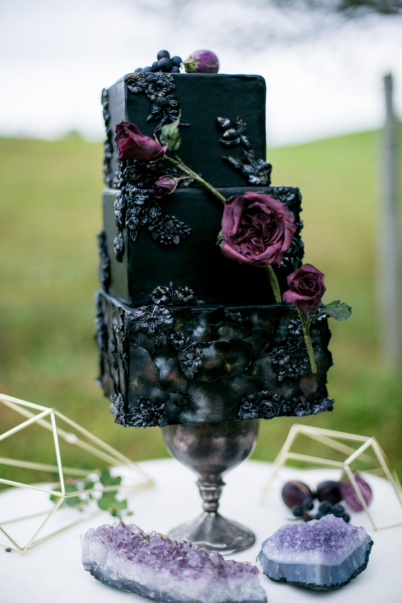 Textured black fondant wedding cake with plum sugar flower
