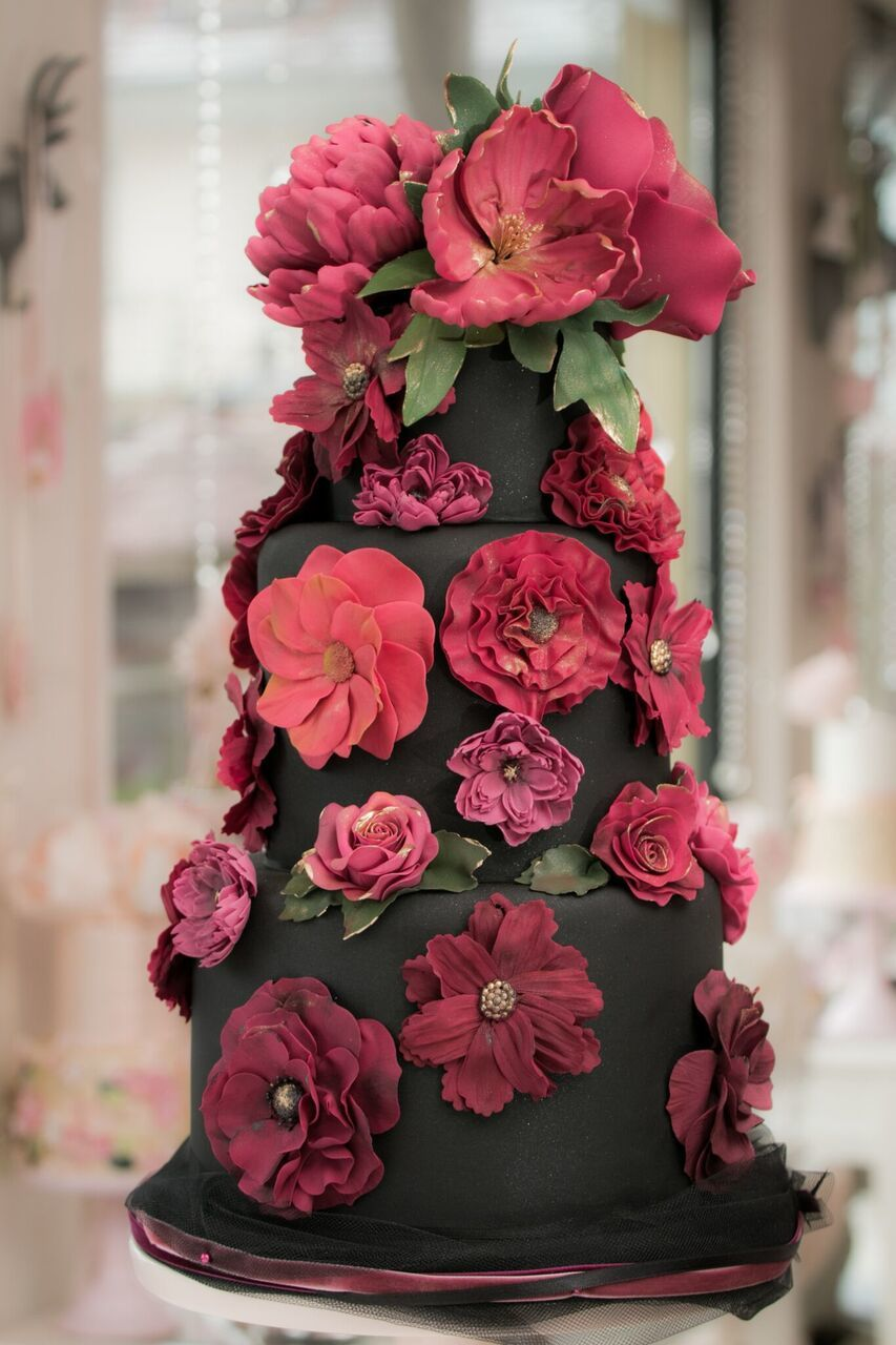 Black wedding cake covered with red sugar flowers