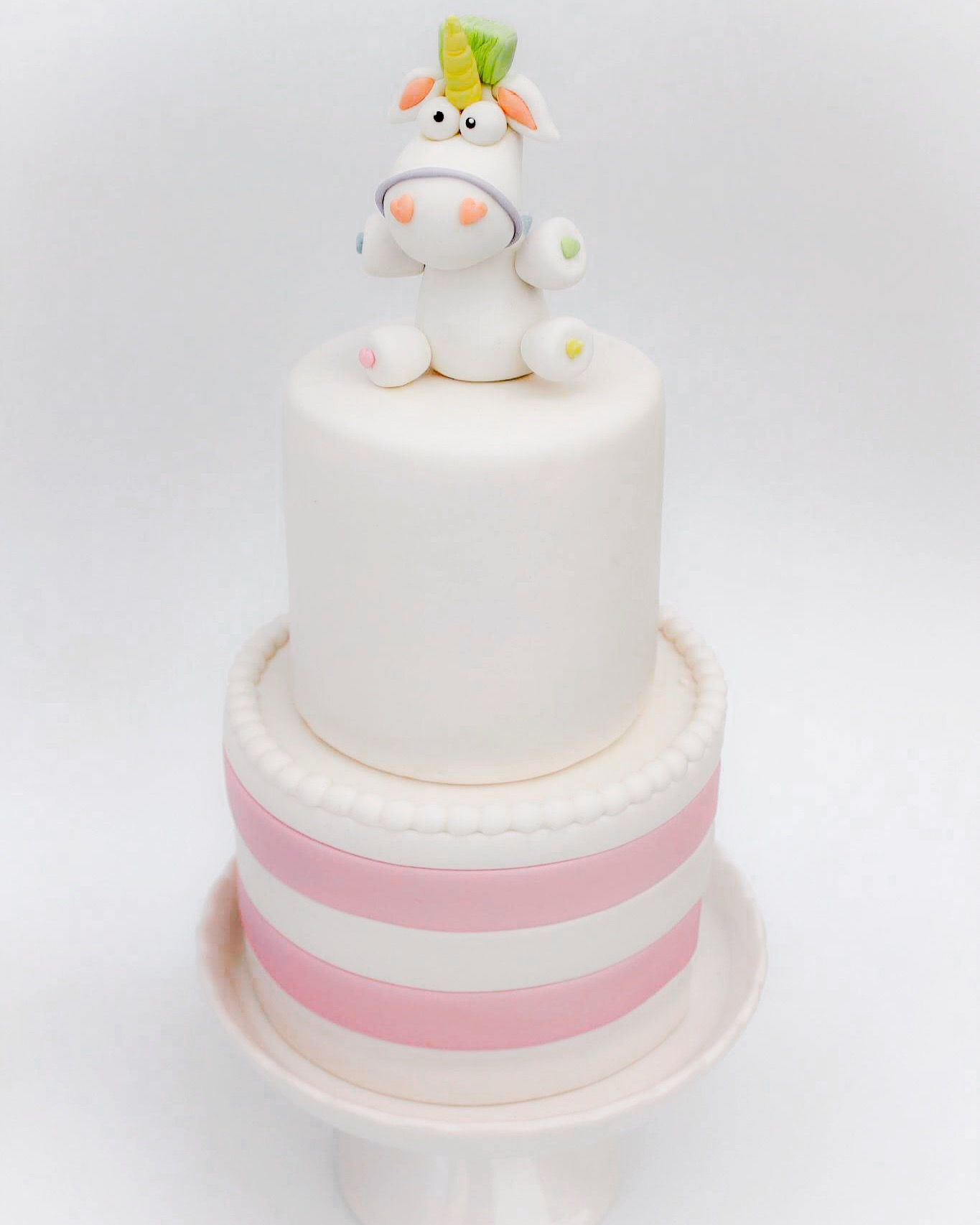 White and pink baby cake with unicorn topper