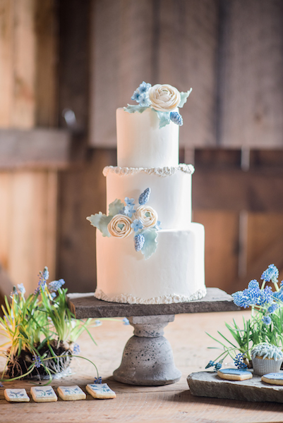 White barn cake with blue sugar flowers