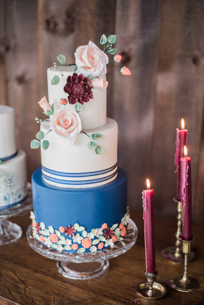 Blue and white wedding cake with burgundy sugar flowers