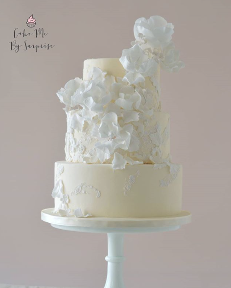 Pastel yellow wedding cake with white flowers
