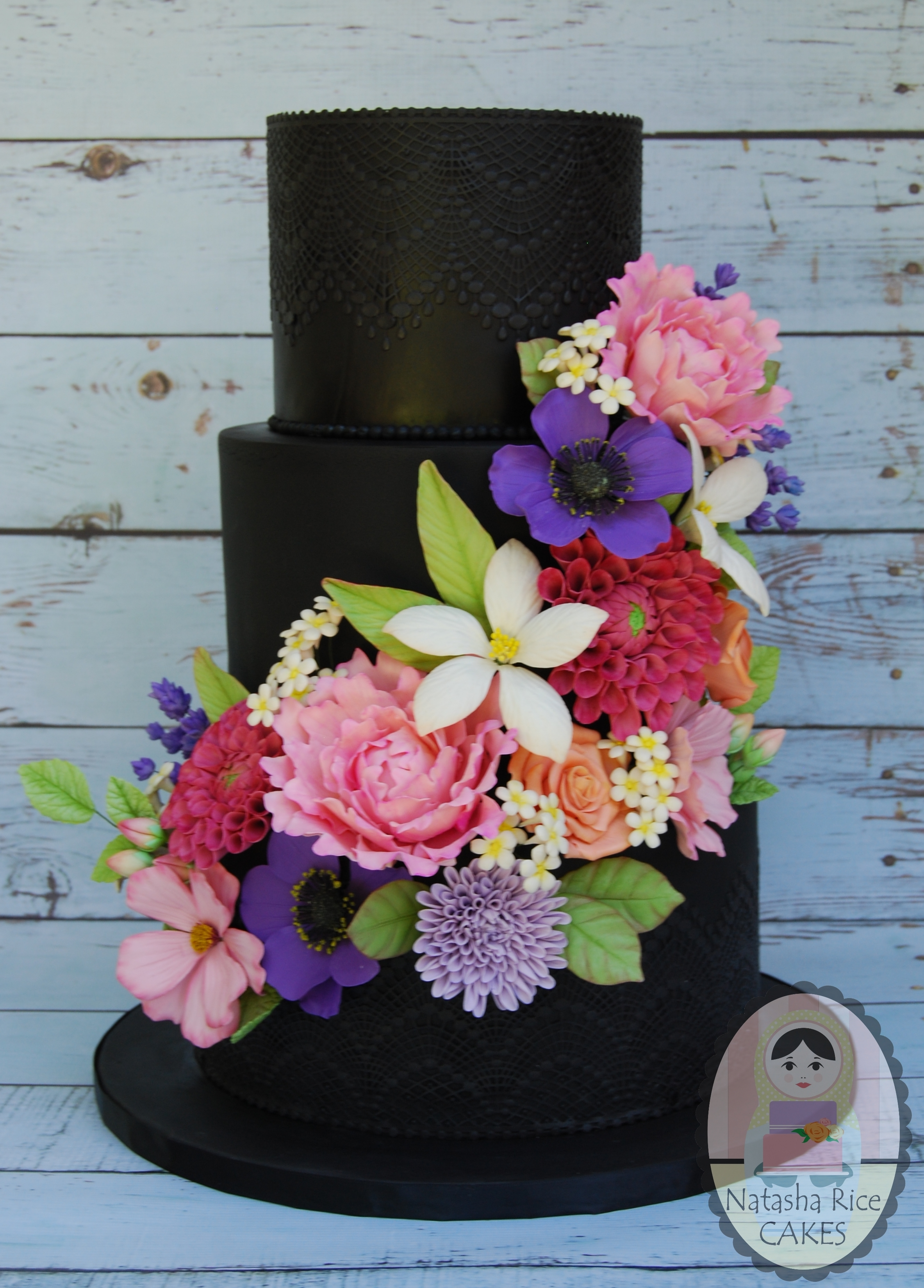 Black wedding cake with colorful sugar flowers