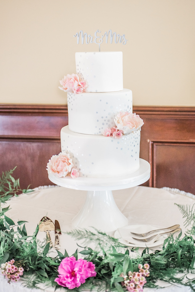 White wedding cake with pink sugar flowers and silver sparkle