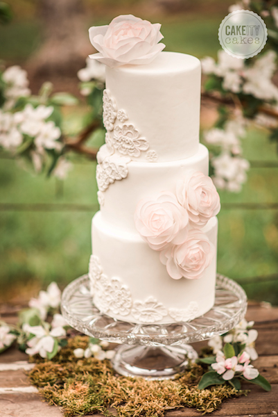 White wedding cake with bas relief design and sugar flowers
